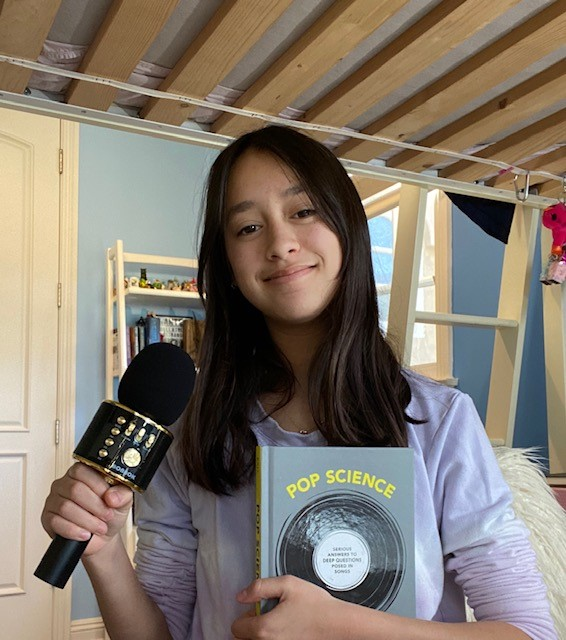 student with microphone and pop music book